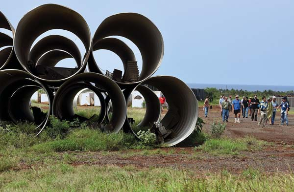 State Land Use Commission members and other attendees of Thursday's site visit of the Pi'ilani Promenade walk past a stack of drainage culverts, which have been stored on the site for years, ever since the previously proposed project was scrapped. The Maui News / MATTHEW THAYER photo