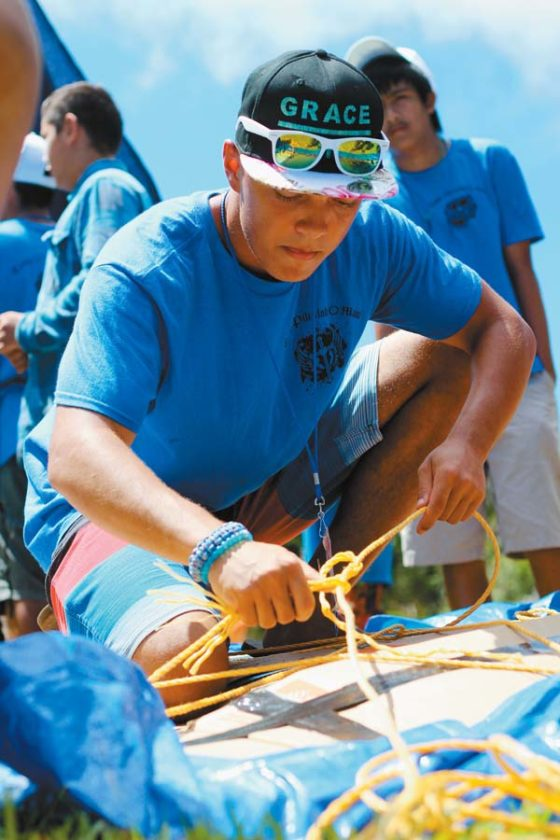 Baldwin High School senior and camp mentor Noah Splajt ties knots to secure the Blue Team's makeshift boat. The Maui News / COLLEEN UECHI photo