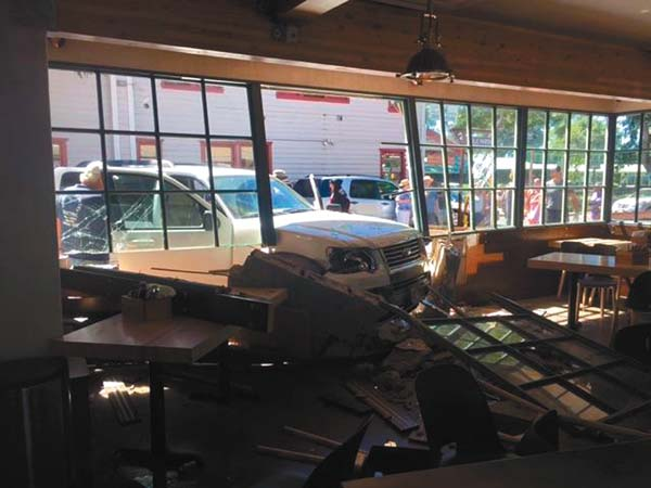 A white SUV is seen partially inside Paia Fish Market on Front Street in Lahaina on Sunday morning. Police said that the SUV's 67-year-old female driver accidentally accelerated and drove into the restaurant, breaking through a window and a portion of the wall. No one was injured. ANATOL EISELE photo