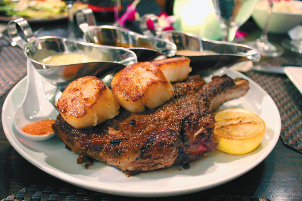 Prime 24-ounce bone-in ribeye steak with a side of Hokkaido scallops. The Maui News / CARLA TRACY photo