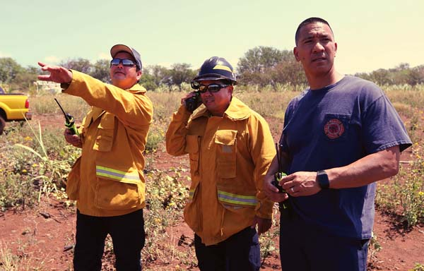 Assistant Fire Chief David Thyne (from left), training Capt. Rylan Yatsushiro and Battalion Chief Amos Lonokailua-Hewett watch a wildland live-fire training exercise Wednesday morning in north Kihei. The Maui News / CHRIS SUGIDONO photo