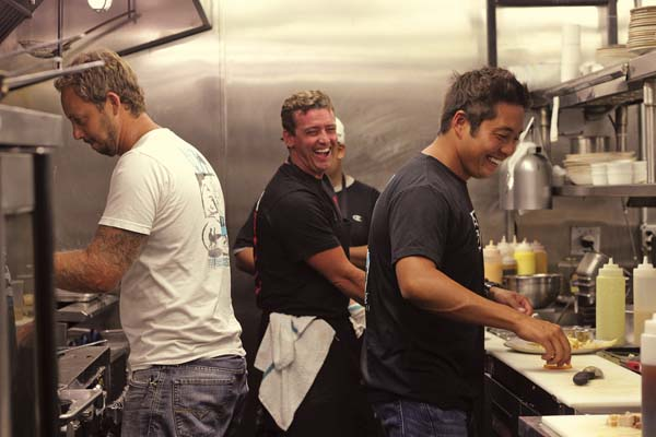 "Chefs and co-owners of Three's Bar & Grill Jaron Blosser (from left), Cody Christopher and Travis Morrin laugh in the kitchen of their Kihei restaurant Tuesday. Six months after a fire damaged their restaurant, Three's was selected to feature on Food Network's ""Diners, Drive-ins and Dives."" Host Guy Fieri visited earlier this month to film with several Maui restaurants, including Three's. Episode dates have not yet been announced. The Maui News / COLLEEN UECHI photo"