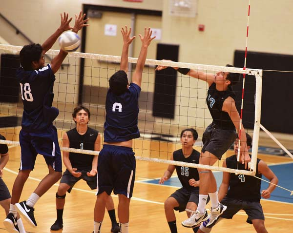 King Kekaulike High School's Nakuluai Morando hits a shot through the block of Kamehameha Maui's Rafael Adolpho and Hanalai Hoopai-Sylva on Thursday night. The Maui News / MATTHEW THAYER photo