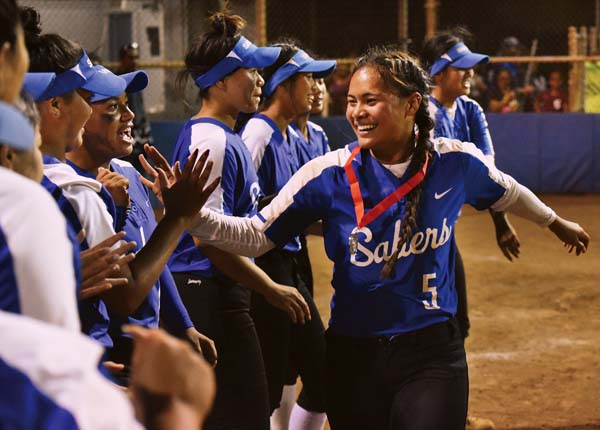 Maui High School's Nawai Kaupe is congratulated by teammates after receiving her MIL runner-up medal Tuesday night at Patsy Mink Field after the Sabers defeated Baldwin 6-4 in nine innings to win the MIL Division I second-place playoff game. The Maui News / MATTHEW THAYER photo