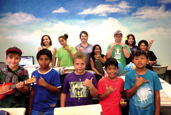 "When she's not writing grants, working with her staff or creating meaningful programs and activities, Lehua Huddleston-Hafoka (back row, center) is keeping a close eye on youth center members — and churning out teachable moments. ""We make time to talk and listen to the kids, because we believe they can do great things,"" she said."