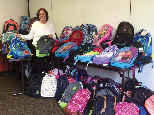 "Realtors Association of Maui member and ""Wishing Well  . . . for Maui Students"" founder Sarah Sorenson poses with a few of the school supply-filled backpacks donated by attendees of the annual President's Circle Conference hosted by the National Association of Realtors' Realtors Political Action Committee."