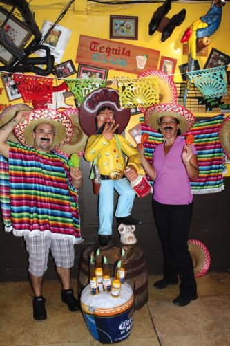 Fred's Mexican Cafe's food runner Mariano Vasquez (at left) and Restaurant Manager Tessa Caskey get in the Cinco de Mayo mood. The Maui News / CARLA TRACY photo