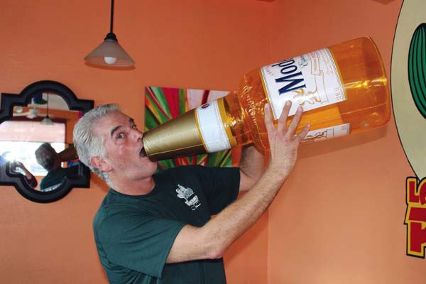 Las Pinatas owner John Hargrove clowns around with a big bottle of Modelo beer, representing one of many Mexican brands he sells at the Kahului restaurant. The Maui News / CARLA TRACY photo