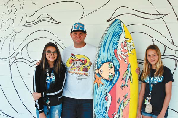 Lily Oldham (left), muralist JoNerZ and Austin Ruppenthal stand in front of their unfinished mural. -- Photo courtesy of Lokelani Intermediate School