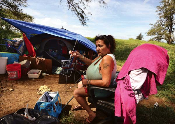 Baldwin Beach Park camper Cindy Gomes sits outside her tent last week and shares her story. About 100 homeless people live around the park, Maui County officials said. The campers have been told they need to vacate the area May 23 after the county received months of public complaints over trash, drugs and disturbances. -- The Maui News / MATTHEW THAYER photo