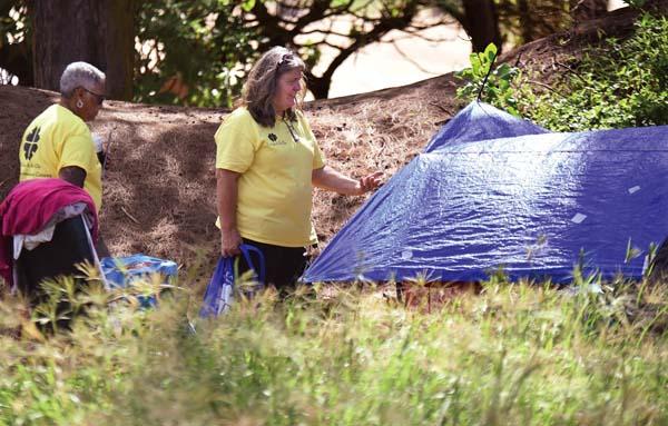 Ka Hale A Ke Ola housing retention specialist Mary Nakooka and housing program director Joy Rucker speak with a Baldwin Beach Park camper. -- The Maui News / MATTHEW THAYER photo