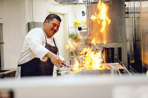 Executive Chef Ikaika Manaku of the Westin Nanea Ocean Villas flames a garlic beef dish on the grill to sear in the juices. Westin Nanea Ocean Villas photo