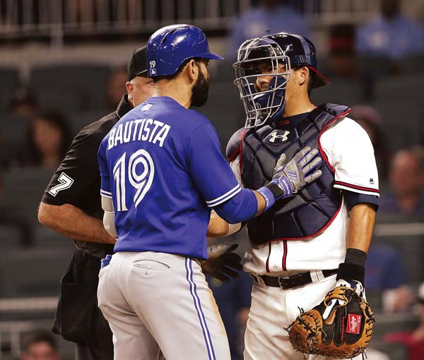 Atlanta's Kurt Suzuki and Toronto's Jose Bautista exchange words after Bautista had rounded the bases on an eighth-inning homer. AP photo