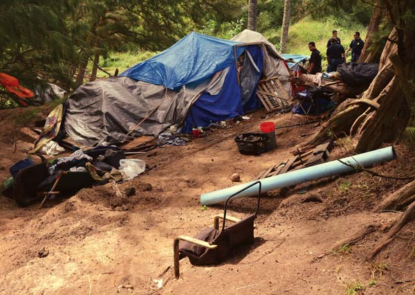 Maui police officers make sure a Baldwin Beach homeless camp is empty of campers Tuesday morning. Many of the homeless people in the camp had left before the 10 a.m. deadline. The area once housed dozens of tents and possibly 100 people. The Maui News / MATTHEW THAYER photo