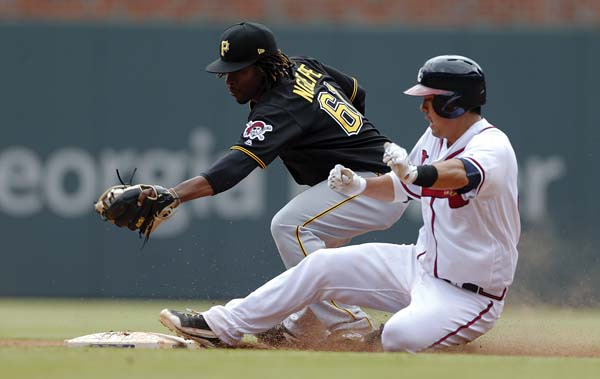 The Braves' Kurt Suzuki is safe at second base with a double as Pirates second baseman Gift Ngoepe handles the late throw in the ninth inning Thursday. AP photo