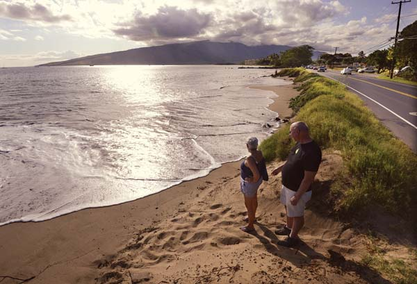 """Kihei residents James Loux and Francine Ally survey the peak of Friday afternoon's """"king tides"""" along South Kihei Road near the Kihei Youth Center. Though he said he was """"unimpressed,"""" Loux did allow that """"obviously it does eat away at the road."""" -- The Maui News / MATTHEW THAYER photo"""