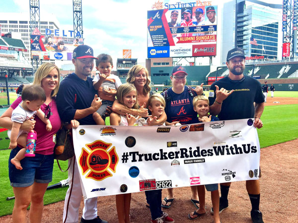 Renee Suzuki (from left), holding son Elijah; Kurt Suzuki, holding son Kainoah; Indiana Dukes; Shauna Dukes; Jedi Dukes; Erin McFarland, a family friend of the Dukeses; Mac Dukes and Joshua Dukes pose for a photo at SunTrust Park in Atlanta on May 19. The Dukeses, who lost 3-year-old Trucker to neuroblastoma in March, are on a tour to visit those who helped the family and to bless strangers along the way in Trucker's memory.