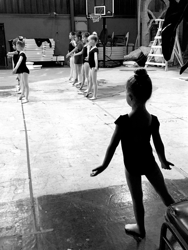 Pasha St. Cyr (lower right), 3 years old, watches and mimics the elementary school-age ballet students of Alexander Academy of Performing Arts  as they rehearse for their year-end show. Chelsea Fine photo
