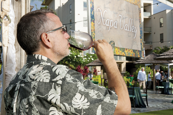 An attendee sips from a world-class selection of wines at the Grand Tasting • KAPALUA WINE & FOOD FESTIVAL photo