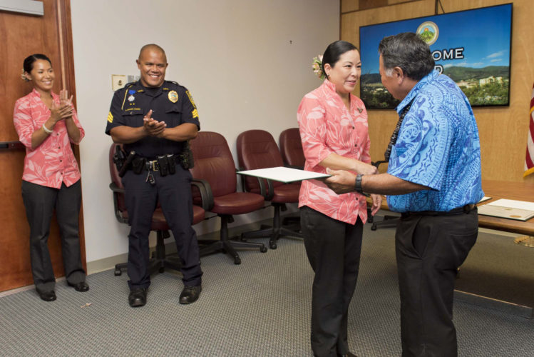 """Mayor Alan Arakawa hands a certificate of recognition to Island Air flight attendant Wendy Nakamura-Chan with flight attendant Shanay Coloma and Maui police officer Kyle """"Ikaika"""" Bishaw-Juario in the background. They were honored Tuesday for coming to the aid of a woman in need of medical attention in the Daniel K. Inouye International Airport Commuter Terminal in March. • County of Maui / RYAN PIROS photo"""