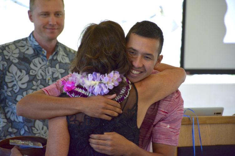 Derek Brown looks on as Ryan Mountcastle receives a hug from Ka Ipu Kukui Fellows Program Director Lori Teragawachi on Wednesday during a graduation ceremony held at the University of Hawaii Maui College. •MARC ANTOSCH photo