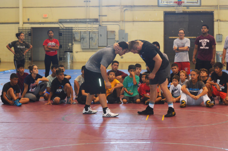 Kyle Snyder demonstrates technique with Jayden Ferreira. • The Maui News / BRAD SHERMAN photo