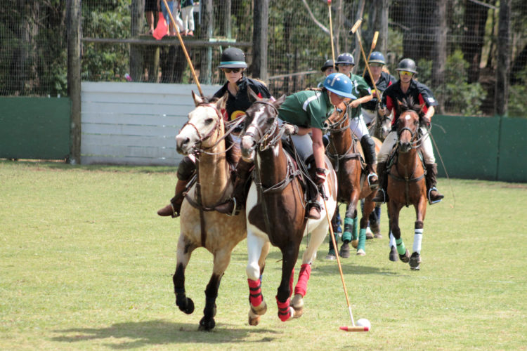 Keala Panzarini of Safari Bloodstock makes a nearside back shot with Laura Coflin of Rising Sun Solar close on defense in the Wahine Arena Challenge on Sunday at Manduke Baldwin Polo Arena. • Coral DeCoite photo