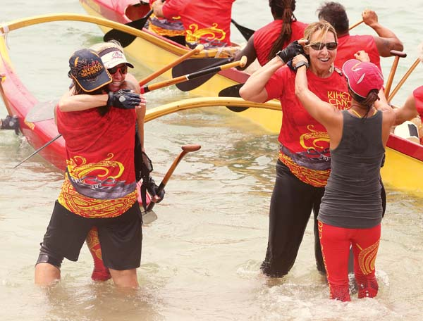 Flori Leon (left, facing camera), hugs Kihei Canoe Club teammate Ellen Federoff as Susan Ramos (right, facing camera) celebrates with Jeanine Masaki after their crew won the women's 50 masters race Saturday in the Moki Kalanikau Regatta at Kahului Harbor. -- The Maui News / CHRIS SUGIDONO photo
