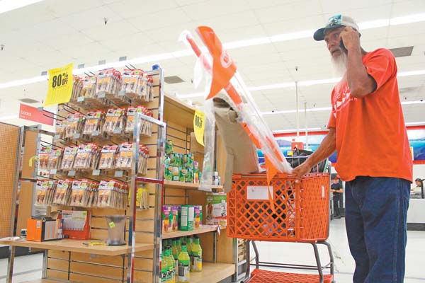 "Wailuku resident and frequent Kmart shopper Leslie Carvalho pushes a cart loaded with items through the store Sunday. ""No more Kmart, no more cheap stuff at local price,"" Carvalho said. The Maui News / COLLEEN UECHI photo"