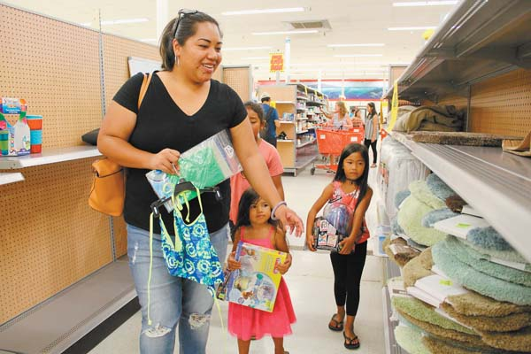 Shyann Lazo of Kahului hunts for deals with nieces Chylee Tacang, 8, Lili'a Sipe-Catiel, 3, and Olena Sipe-Catiel, 6, in Kmart on Sunday. The Maui News / COLLEEN UECHI photo