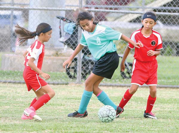 Ohana Grown's Poerava Brewster dribbles between Maui United's Krychalei Loui (left) and Kaylia Hema in their under-10 girls match at the Maui No Ka Oi Tournament on Wednesday at the Eddie Tam Complex in Makawao. The Maui News / CHRIS SUGIDONO photo