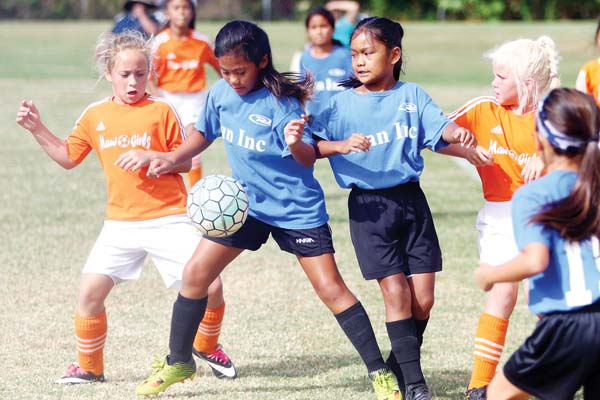 The Maui Girls' Devlin Freitas battles for a ball against Rush Maui's Kili Kamakeeaina alongside Kaley Alconcel and Averi Hatch during their under-10 girls match Friday at the Maui No Ka Oi Tournament on Friday in Makawao. -- The Maui News / CHRIS SUGIDONO photo