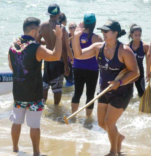 Shahlia Wainui, one of Na Kai Ewalu's keiki coaches, high-fives head coach Owen Seiki after the John Wilmington III sophomore women's race Saturday at Kahului Harbor. -- The Maui News / ROBERT COLLIAS photo