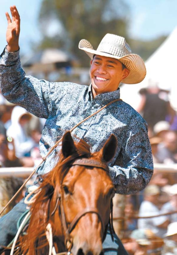 Tristan Hooper waves to the crowd while taking a victory lap after winning the tie-down roping buckle. The Maui News / MATTHEW THAYER photo