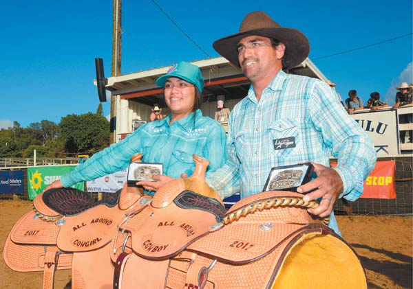 Brad Apo and daughter Lehiwa Apo pose with their Makawao Rodeo all-around cowboy and all-around cowgirl saddles Sunday afternoon at Oskie Rice Arena. The Maui News / MATTHEW THAYER photo
