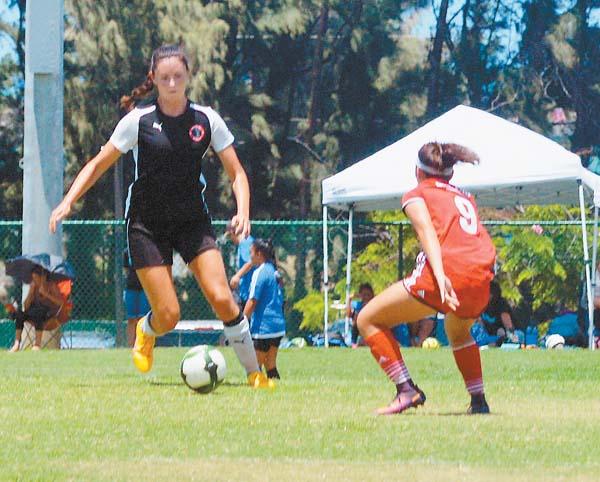 Maui United's Mihana Ho is marked by the Galaxy's Mia Anzalone. The Maui News / BRAD SHERMAN photo