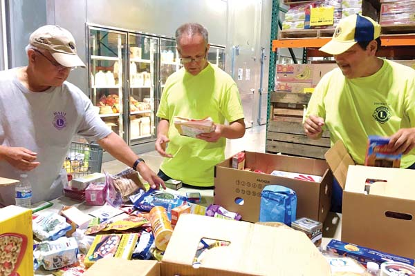Past District Gov. Joe Pontanilla (from left), Zone Chairman David Rudd and past District Gov. Mark Mizuno check dates and sort nonperishable goods at the Maui Food Bank. The six Lions Clubs on Maui helped prepared 11 pallets of food for distribution.