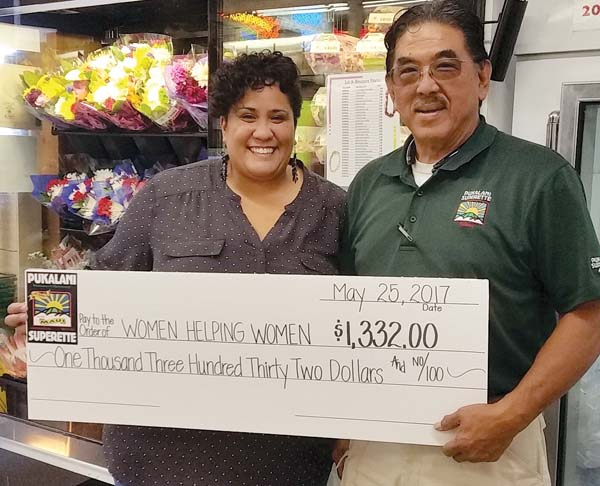 Sanoe Kaaihue, acting executive director of Women Helping Women (left), accepts a check for $1,322 from Aric Nakashima, co-owner of Pukalani Superette. An additional $543.75 was donated individiually to four elementary schools.
