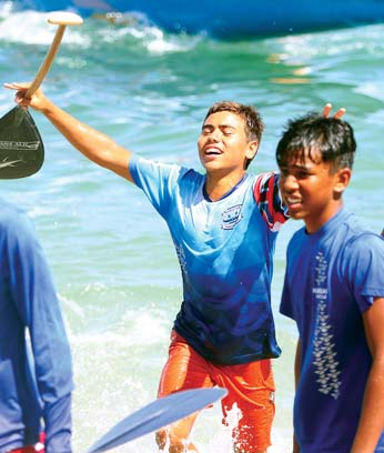 Isaac Sambrana holds up his paddle in celebration as he and Kana'i Fisher return to shore after helping Hawaiian Canoe Club win the John M. Lake Regatta boys 13 race Saturday at Kahului Harbor. -- The Maui News / CHRIS SUGIDONO photo