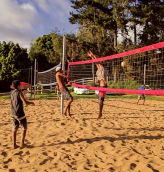 Hinano Long spikes a ball past Kala'i Anderson while Austin Peters looks on during an Aloha Volleyball match Saturday in Kula. Long and Peters won the 18 boys division. -- SCOTTIE ZUCCO photo