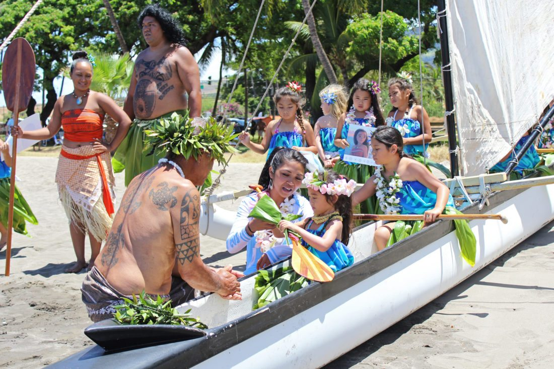 Six-year-old Aliyah Nitta examines a gift of a paddle alongside her auntie Vanessa Bascar-Fernandez and cultural practitioner Kimokeo Kapahulehua on Sunday at Launiupoko Beach Park. Dream Imua, a local wish-fulfilling program for children, gave Aliyah a daylong celebration inspired by her favorite Disney character, Moana.  • The Maui News / COLLEEN UECHI photo