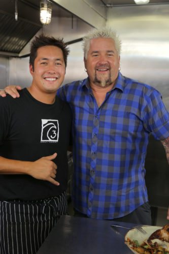 "Three's Bar & Grill partner Travis Morrin (left) with Guy Fieri during a taping of ""Diners, Drive-Ins and Dives"" for the Food Network. • Photo courtesy ""Diners, Drive-Ins and Dives"""