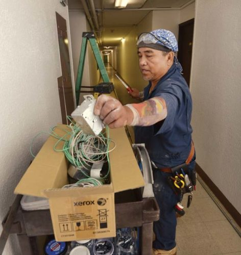 Sea Breeze Electric owner Nick Casumpang installs boxes and conduit while wiring a smoke alarm system in Harbor Lights Building D on Tuesday afternoon. Since the deadly Grenfell Tower blaze in London a month ago, unit owners have been working to update fire safety measures. -- The Maui News / MATTHEW THAYER photo