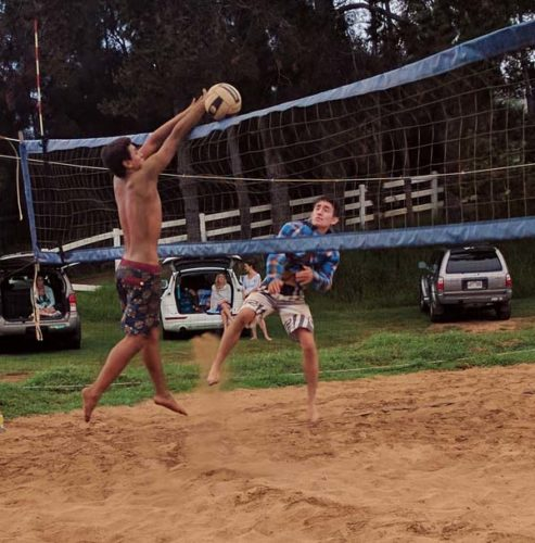 Noah Rohozinski spikes a ball against a Hinano Long block during an Aloha Volleyball 18 boys match Saturday. -- SCOTTIE ZUCCO photo