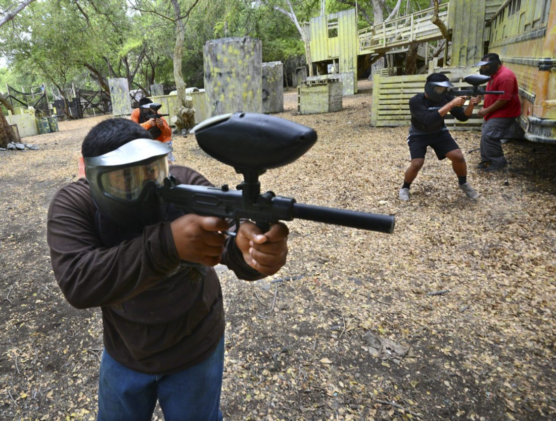 MPD Teen Academy cadets Koapaka Purdy (from left), Gavin Arista and Kylsan Morton return fire during a training simulation last week after being fired upon during a traffic stop at the Maui Paintball facility in Olowalu. Taking cover behind a bus is police Sgt. Lawrence Pagaduan. • The Maui News / MATTHEW THAYER photo