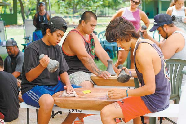 Maui High School student Kaimana Benjamin (left) and Maui Tempeh employee Charles Revard pound kalo into pa'i'ai Sunday at the Maui Nui Botanical Gardens. The nonprofit Lo'iloa organized the ku'i, or kalo pounding, in honor of La Ho'iho'i Ea, Sovereignty Restoration Day. The Maui News / COLLEEN UECHI photo