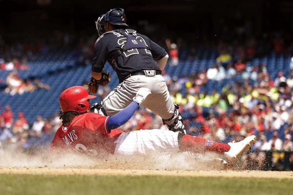 The Phillies' Freddy Galvis scores past Braves catcher Kurt Suzuki in the fourth inning of Atlanta's 7-6 loss Monday. AP photo