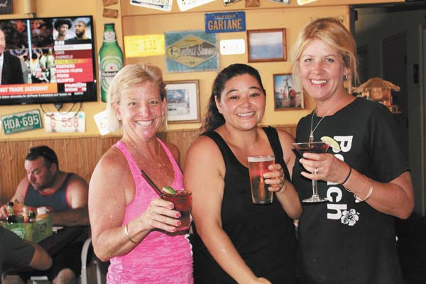 Beach Bums BBQ & Grill servers Kim Berry (from left), Maile Cote and Abby Hatfield serve daily happy hour libations from 3 to 6 p.m. and through live music from 5 to 8 p.m. nightly in Maalaea. The Maui News / CARLA TRACY photo
