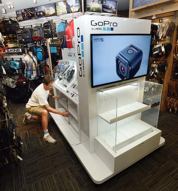 Hi-Tech Surf Sports owner Kim Ball inspects a thick plexiglass GoPro display case that was smashed during a burglary Thursday morning at the Kahului shop. The Maui News / MATTHEW THAYER photo
