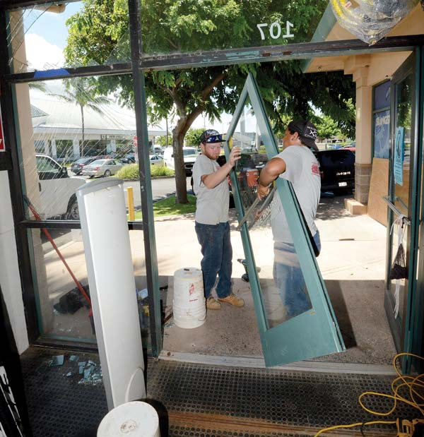 Sam Lincoln and Lama Pupuhi of Lincoln Construction rehang a door at Hi-Tech Surf Sports on Thursday morning in Kahului. Thieves used a stolen vehicle to smash open the doors to gain access to the store where they raided a GoPro case stealing aerial drones and cameras. The Maui News / MATTHEW THAYER photo